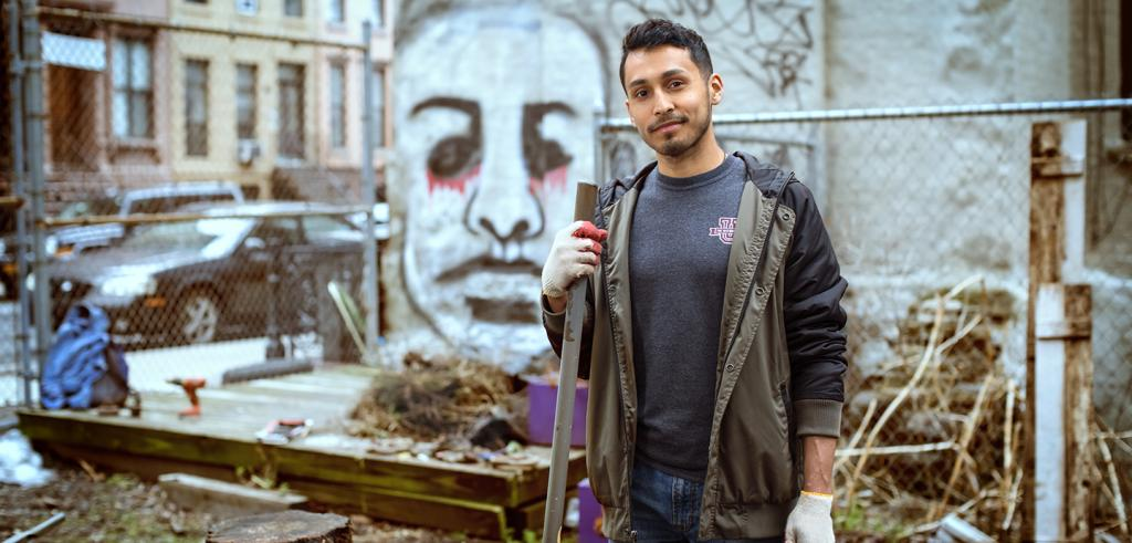 Alec Martinez standing with shovel in a derelict lot in harlem, ny