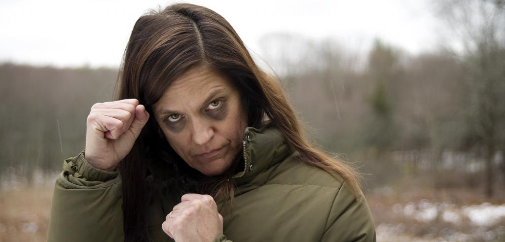 Image of a woman standing outside wearing a winter coat with fists raised and two black eyes.