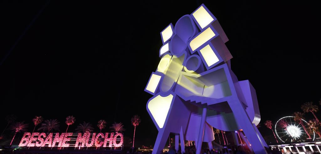 Large interactive sculpture installation illuminated with purple and yellow light, Besame Mucho in red letters in lower left
