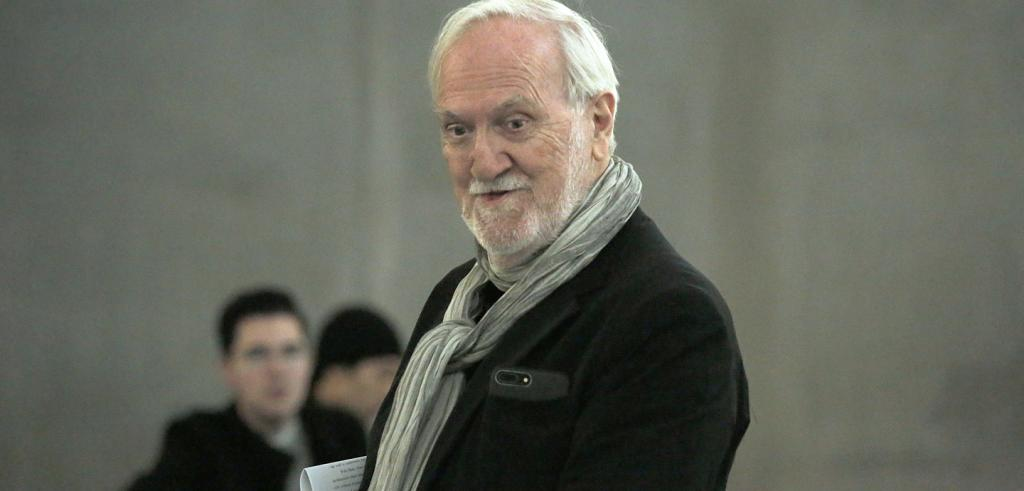 Man with gray hair, gray beard and neck scarf listening.