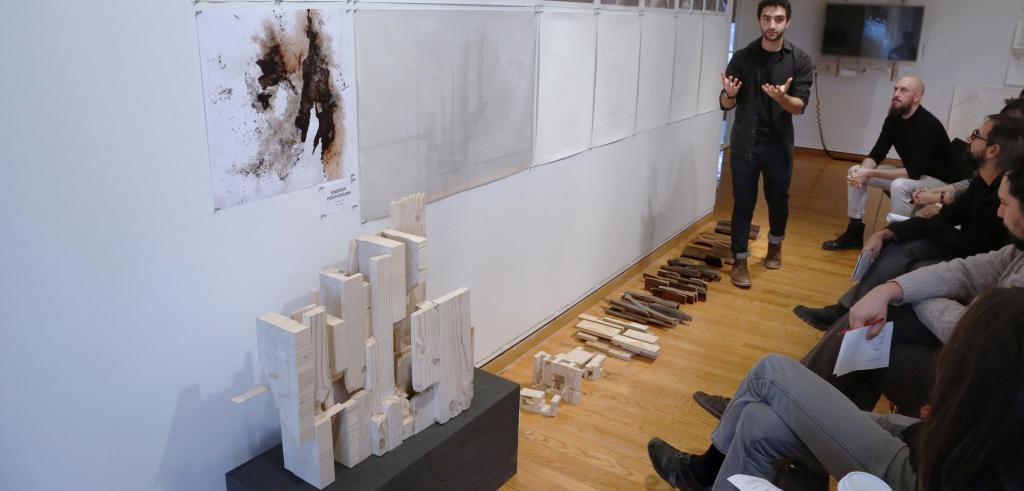 Man gesturing towards a wooden model with people watching.