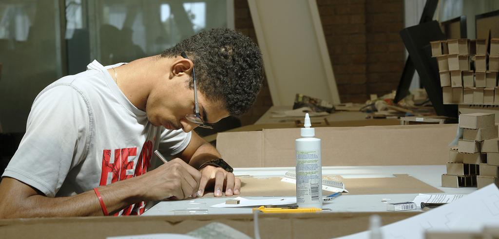 student working in studio at a desk with glue and cardboard models