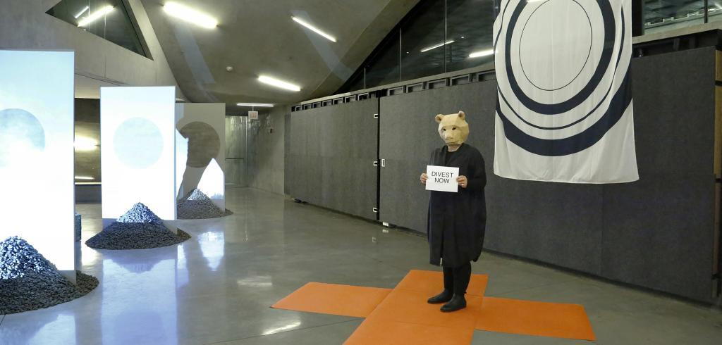 A person wearing a bear mask standing in a room holding a sign