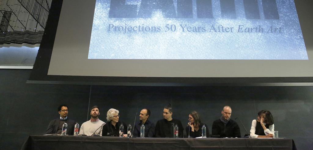 a row of people seated at a table with a screen behind them showing Earth Projections 50 Years After Earth Art