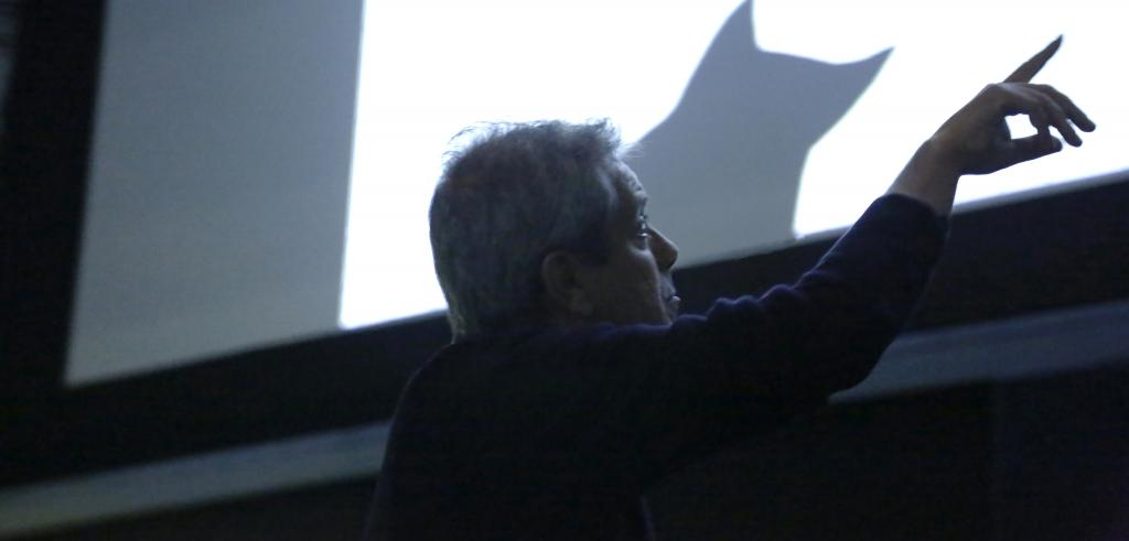 Man pointing towards a projection screen.