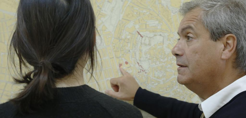 Man pointing to a map speaking to a woman.