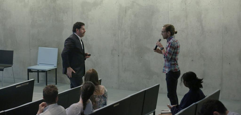 Two men talking in an auditorium, one is holding microphone