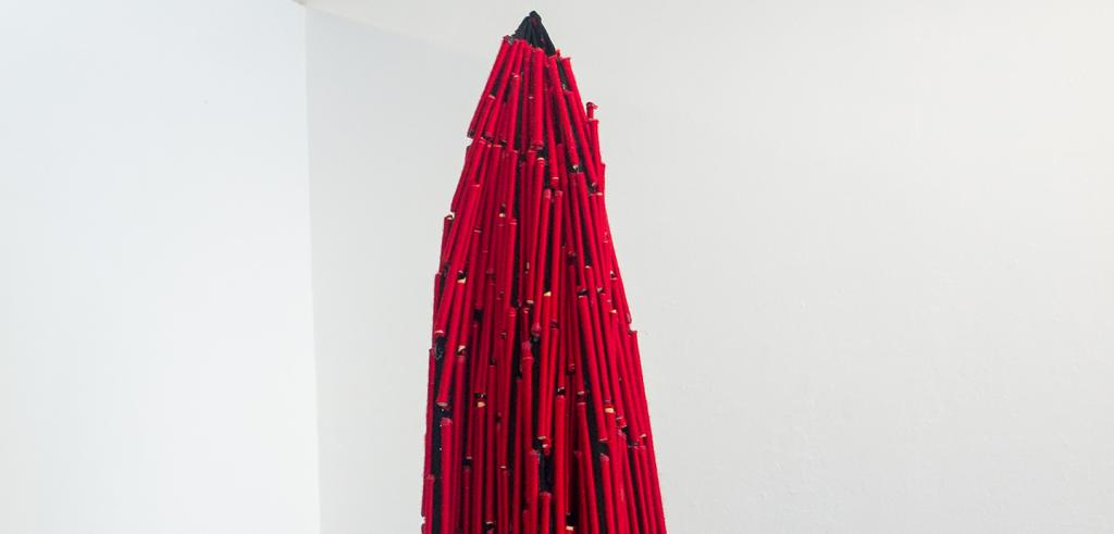 Red and black fabric sculpture piece hanging from the ceiling.