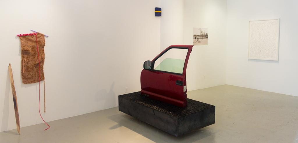 A single car door on a black platform on display near a hanging knitted artwork with three other pieces on the wall.