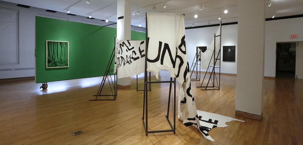 Cloth banners mounted on steel armatures and framed in an art gallery.