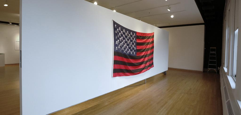 A replica of an American flag hanging on a long white wall