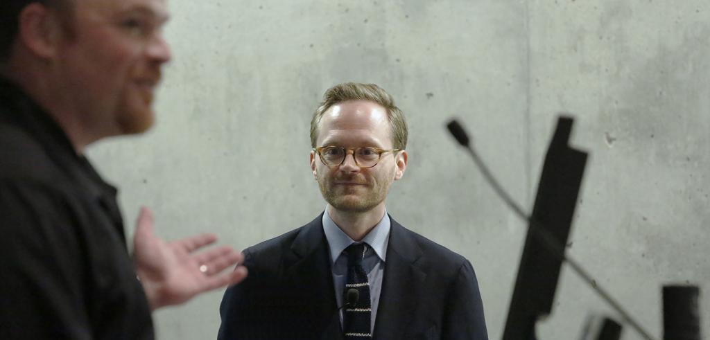 Man gesturing toward another man wearing glasses.