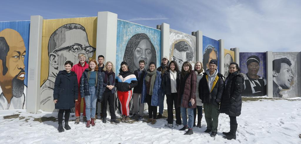 a group of people standing in from of a mural in winter