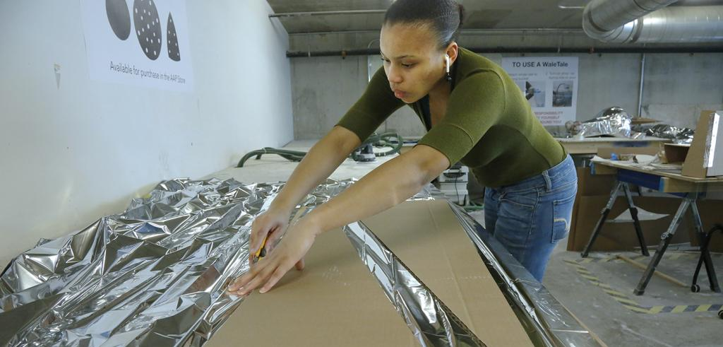 young woman works to trim reflective fabric around a cardboard cut out