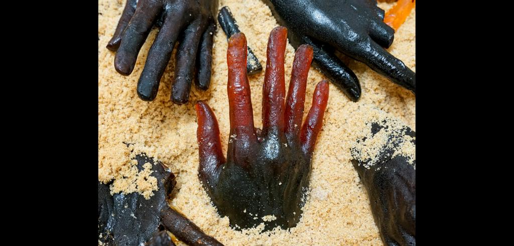 Sculptures of dark red colored hands partially buried in sand.