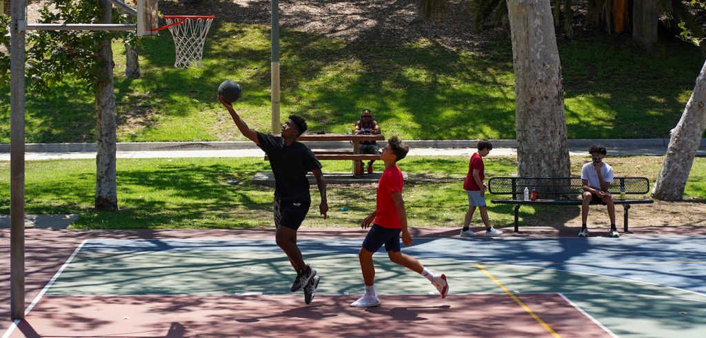 teenagers playing basketball in a park with people watching from benches