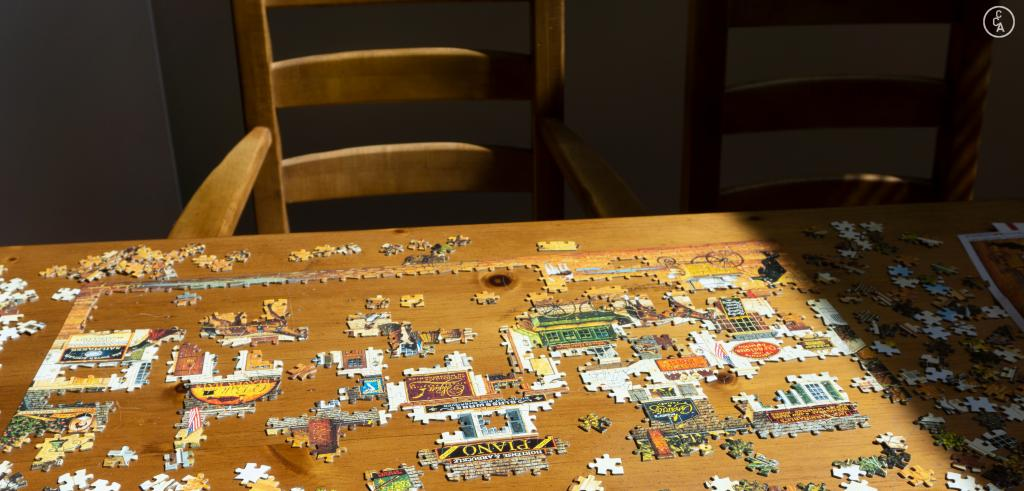 Puzzle partially put together on a wooden table with a wooden chair in a shadow.