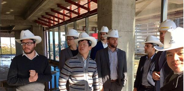 Students wearing cowboy-style hard hats at a contraction site