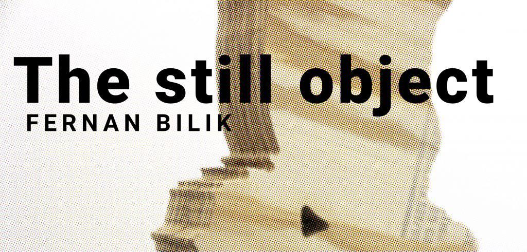 Wooden abstract figure set behind the words 'the still object fernan bilik'.