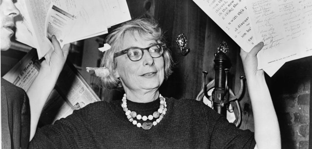 woman with glasses, dark sweater and beaded necklace with hands full of papers