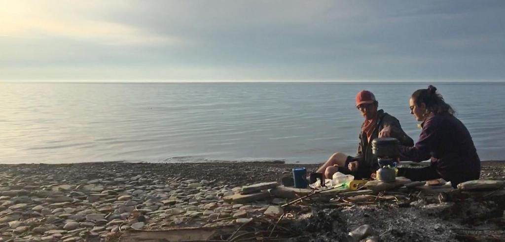 Two people sit with a camp stove on a rocky beach.