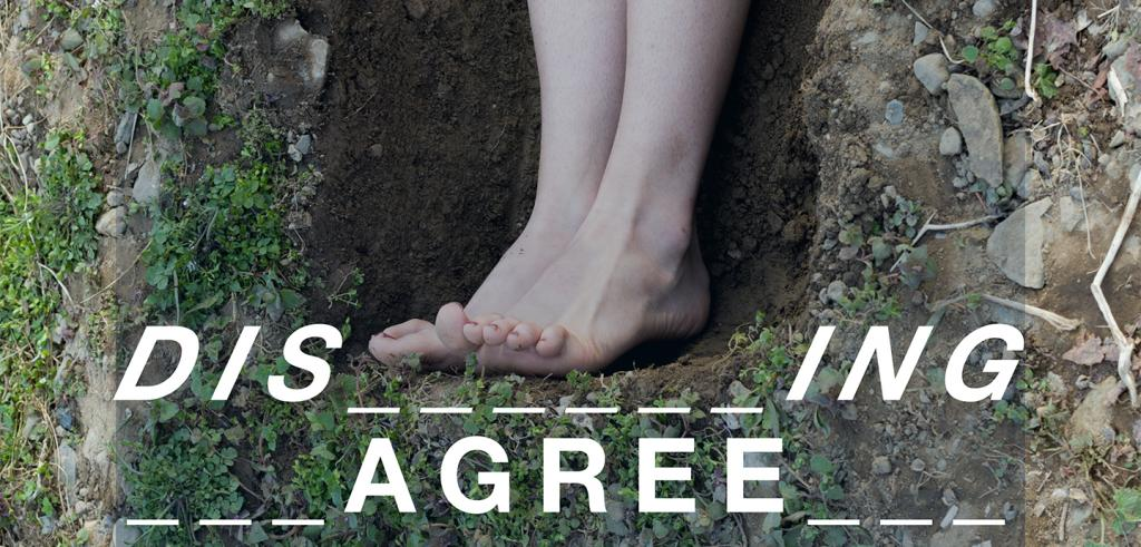 Two feet standing in a dug hole surrounded by grass, rocks, and dirt with the title 'Disagreeing' spelled with lines and in white letters beneath it.