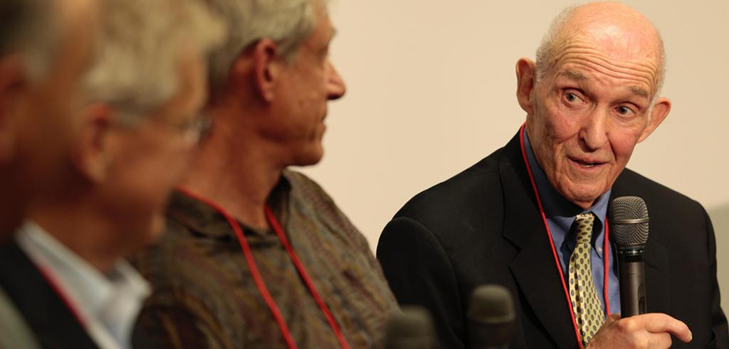 three people in the foreground looking at Don Greenberg who is holding a microphone