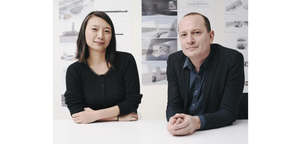 A man and a woman, each in black tops looking at the camera, with a wall of architectural renderings behind.