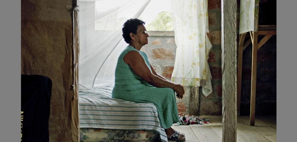 Woman wearing a green dress sitting on a bed with blue and white striped sheets near a window with a blowing curtain around it.