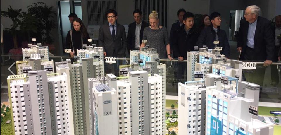 People standing behind a scale model of city skyscrapers