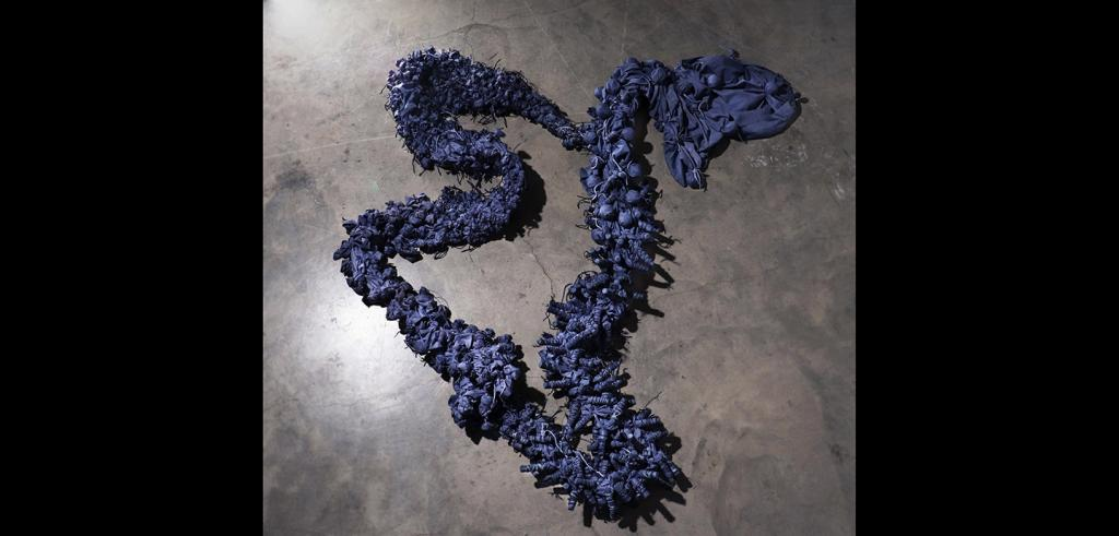 Pieces of dark purple cloth bound together with dark purple yarn in bunched up patterns.