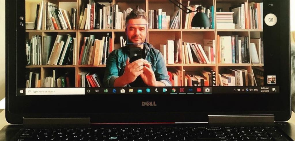 Man taking a selfie displayed on a laptop computer screen with bookshelves behind him.