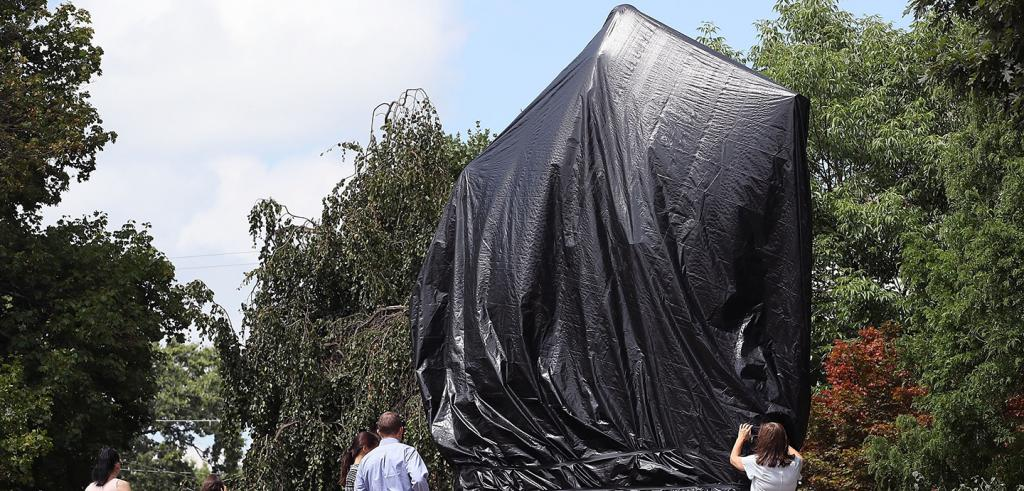 An installation located in a public garden, covered by a large, black tarp