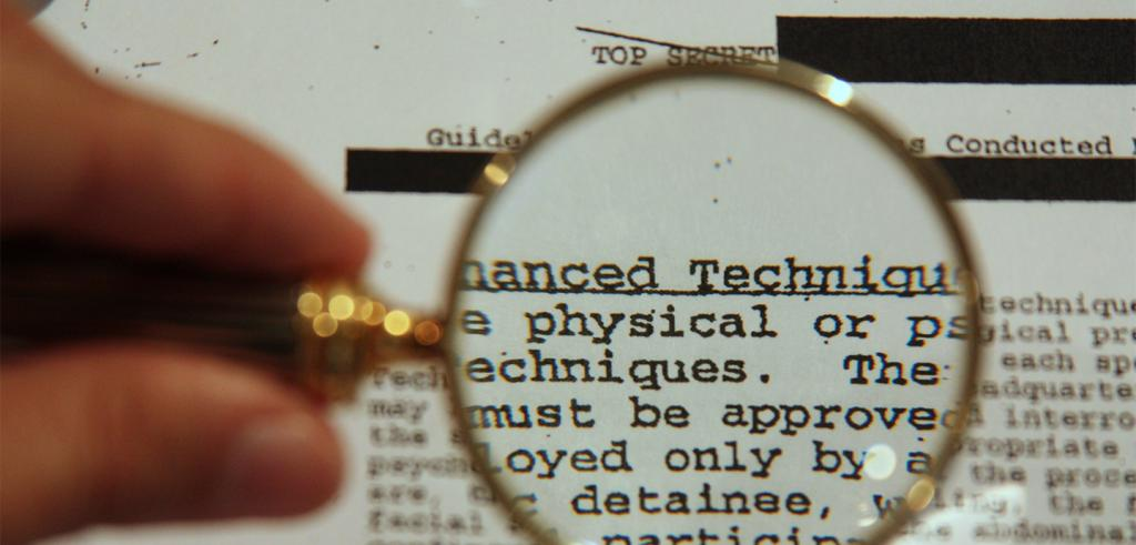 A blurry hand holding up a gold magnifying glass over typed words on a page.