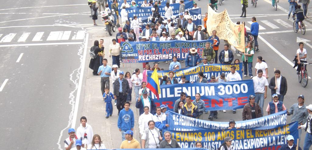 An aerial view of a crowd of people marching with large blue banners.