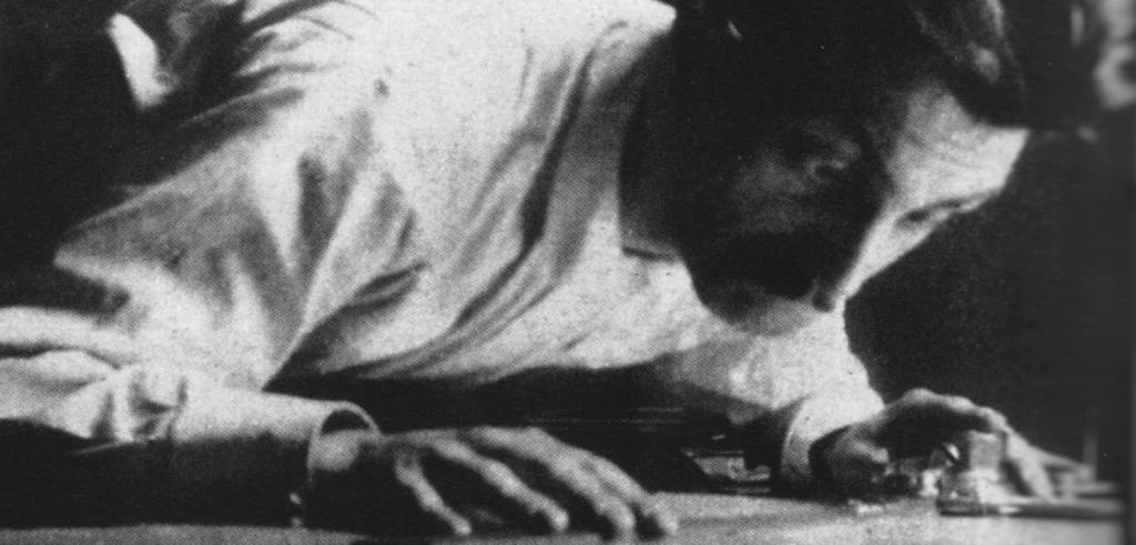 grainy black and white photo of a man leaning over a table top