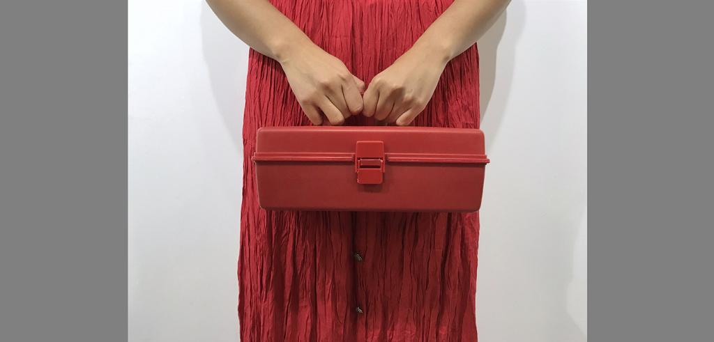 Two hands holding a red toolbox over a red skirt.