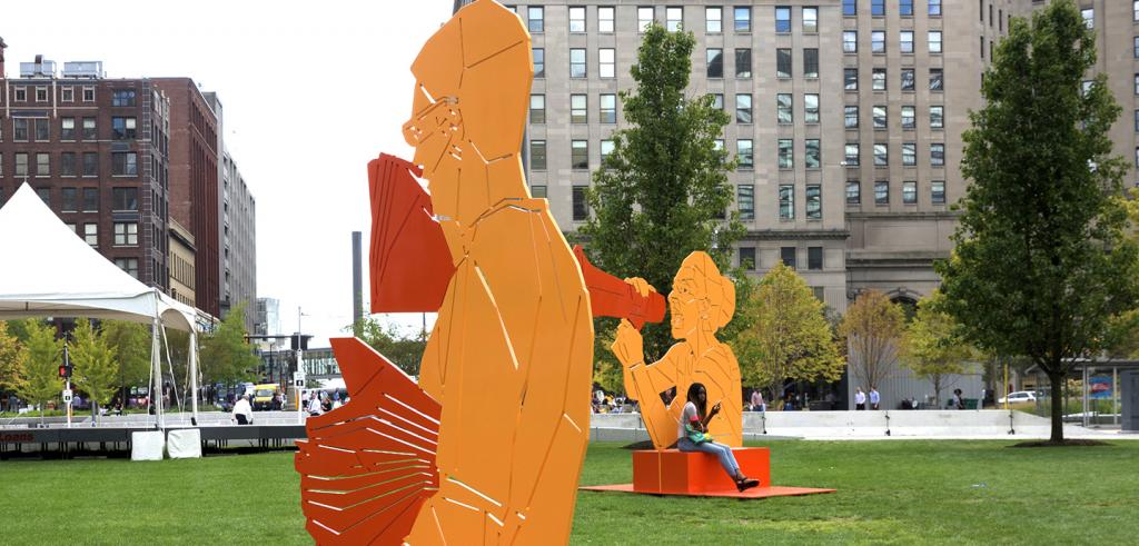 a photograph of an urban park two yellow and orange public sculptures, a woman seated and buildings in the background