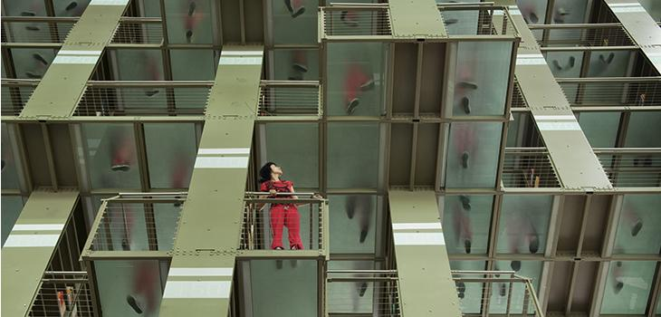 Figure in red standing on a mid-level landing in a building.