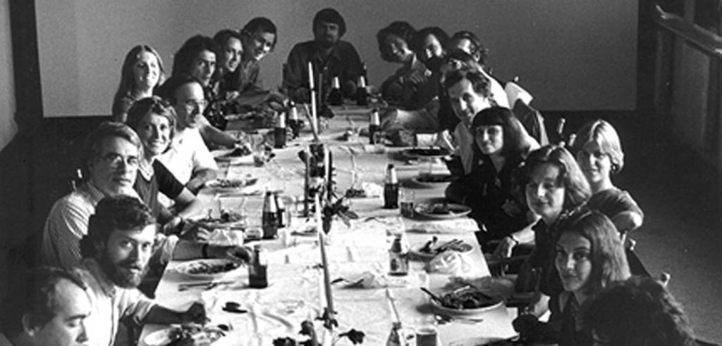 Black and white photo of people gathered around a dinner table looking into the camera.