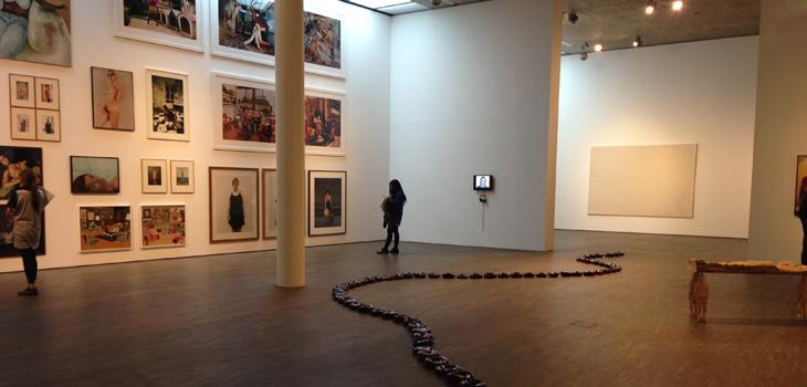 student in an art museum with paintings on the wall and a snake-like sculpture on the floor