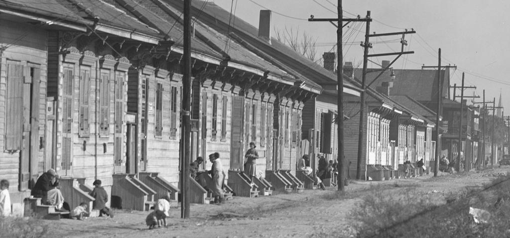 Old black and white photo of people and houses
