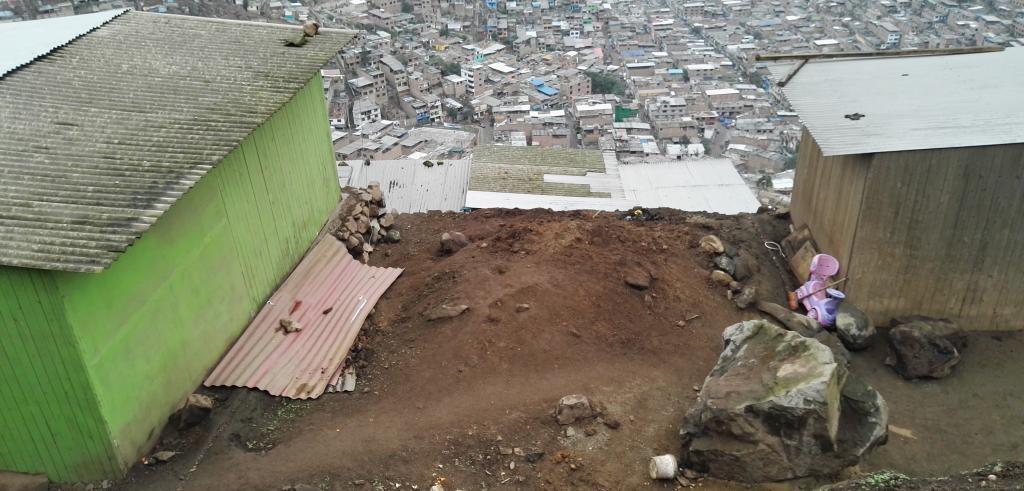 view between two huts set on a hill overlooking an informal settlement