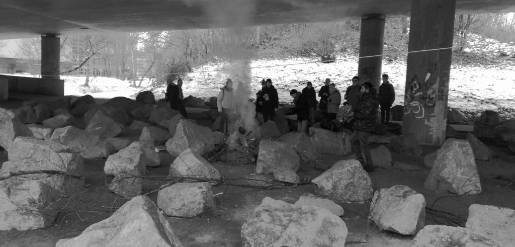 a group of people around a small fire in a group of rocks under an overpass
