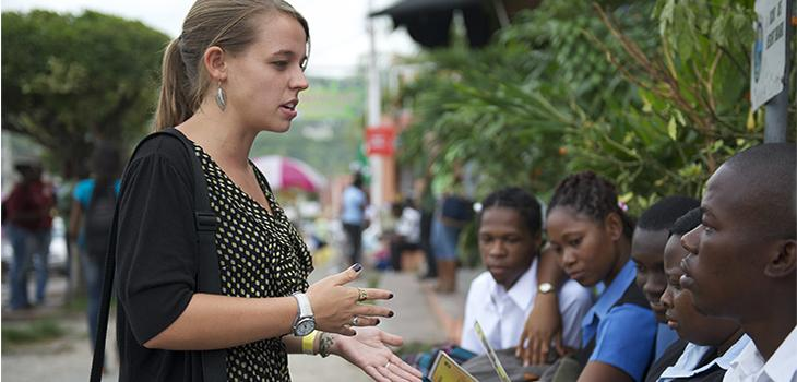 Photograph of a young woman speaking with locals