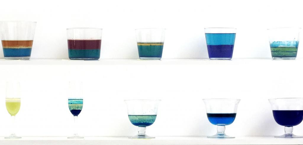 Two shelves of cups full of different colors and levels of liquids