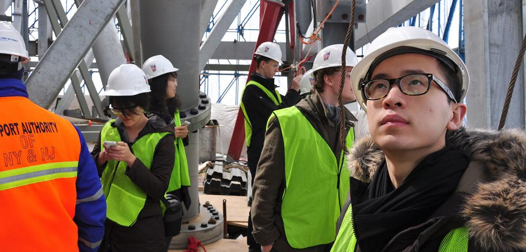 A close-up of students in hard hats and neon vests touring a structure under construction.