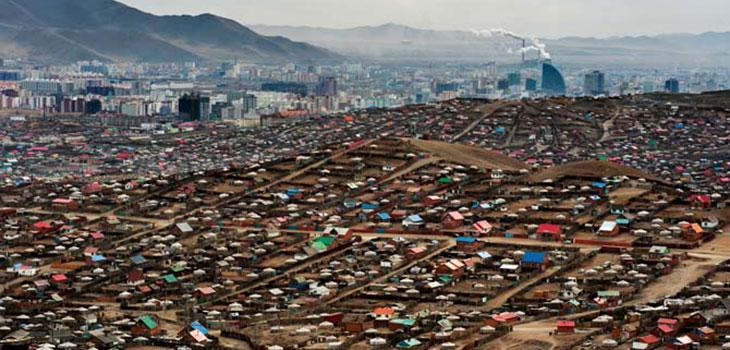 Cars parked outside of a mountain-bordered city