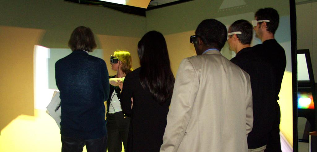 a group of people looking at an on-screen VR demonstration in a room