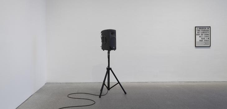 Speaker on a stand in a white room with a framed picture on the wall